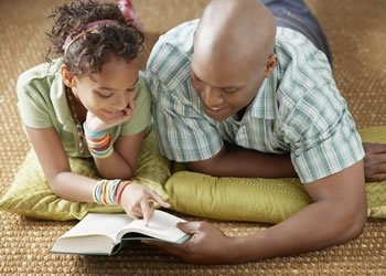 A father reading with his Daughter.