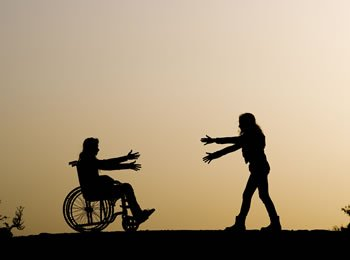A person in a wheelchair and another person reaching out to each other.
